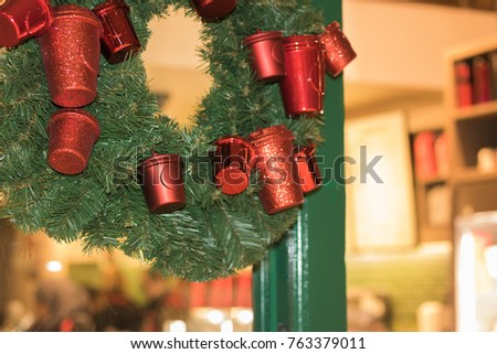 A wreath of green branches of Christmas tree with red toys in a shape of buckets is hanging on a glass door of a café in evening. Concept: Christmas and New Year door decorations.