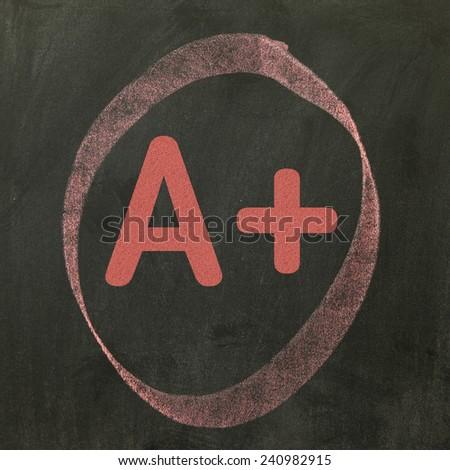 A+ Written on a blackboard - stock photo