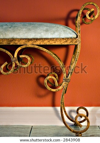 A Wrought Iron Bench Against A Red Wall - stock photo