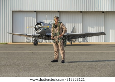 A WWII military pilot with his SNJ5 aircraft returning from a mission - stock photo