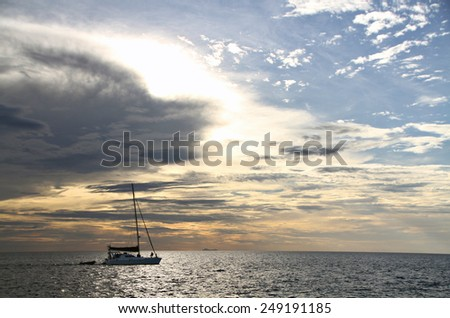 A yacht cruises along as the sun sinks towards the horizon.  - stock photo