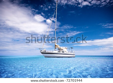 A Yacht travelling through crystal clear tropical waters - stock photo