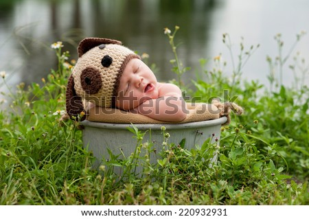 A yawning three month old baby boy wearing a crocheted puppy dog hat. He's sleeping in a galvanized steel bucket that's placed outside in a patch of wildflowers growing near a lake. - stock photo
