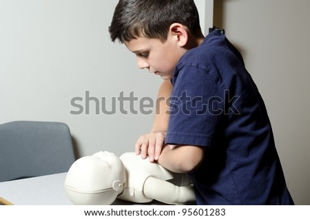 a 9 year old boy giving CPR to a pretend baby. - stock photo
