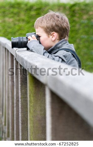 A 9 year old boy is practising with his fathers camera. - stock photo