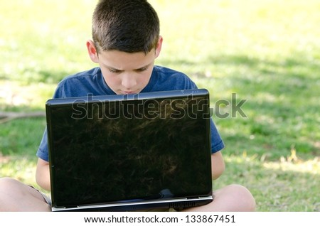 A 10 year old boy looking at his computer screen while sitting in the park. - stock photo