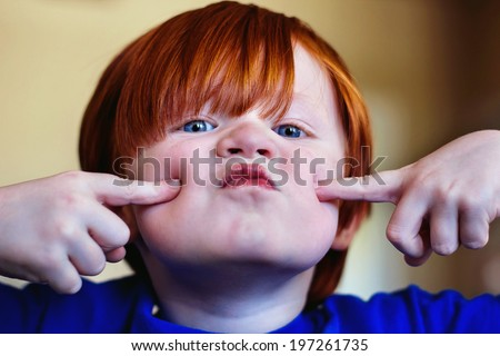 A 4 year old boy making funny faces and being silly -- image taken indoors using natural light  - stock photo