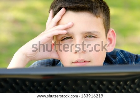 a 10 year old boy with his hand on his head as he looks over the lap top computer screen. - stock photo