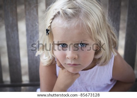 A 5 year old child looking seriously at the camera. Soft focus on background - stock photo