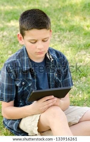 a 10 year old child with his tablet in the park. - stock photo