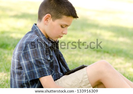 a 10 year old child with his tablet in the park.