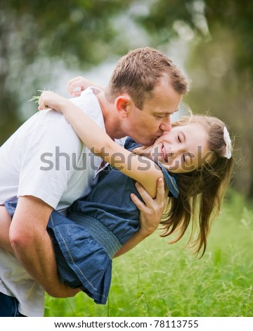 A 6 year old girl enjoying a moment of fun with her dad who is kissing her on the cheek. - stock photo