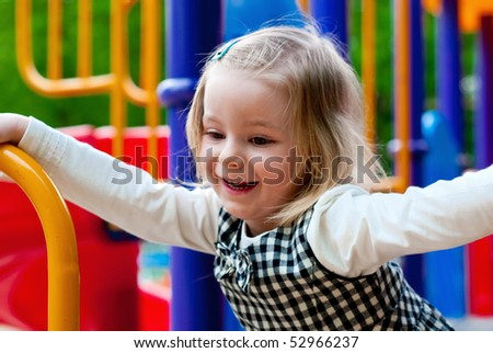A 3 year old girl in playground equipment - stock photo