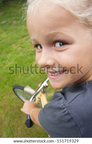 A 6 year old girl on a bike learning to ride. Shot from top in different angle - stock photo