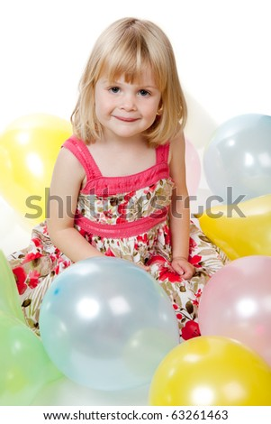 A 4 year old girl sitting and looking at camera whilst playing with some multi-coloured balloons.