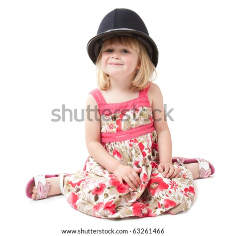 A 4 year old girl sitting and looking at camera whilst wearing a British police helmet.