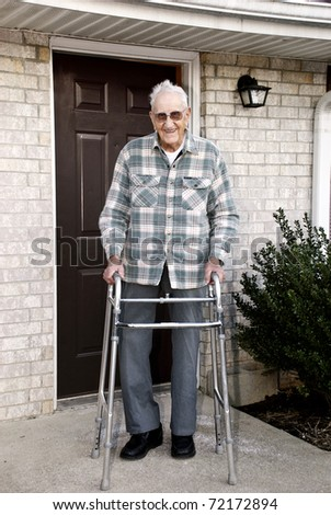 A 93 year old handicapped man, with a walker, standing outside in front of his apartment - stock photo