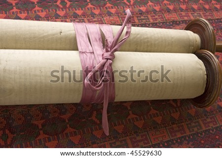 A 150 year-old vintage torah scroll tied with a faded purple ribbon to keep it from unrolling. - stock photo