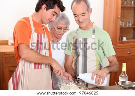 a 20 years old boy and 65 years old man and woman making cake together