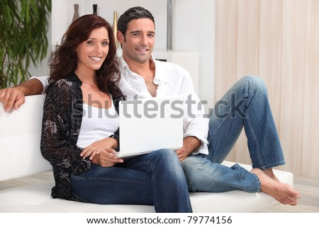 a 35 years old couple sitting on a couch - stock photo