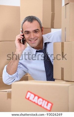 a 40-45 years old employee calling someone in a room full of cardboard boxes - stock photo