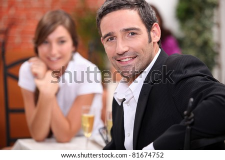 a 40 years old man and a 16 years old girl with sparkling wine on a restaurant table - stock photo