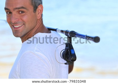 a 40 years old man walking on the beach with a fishing rod on his shoulder - stock photo