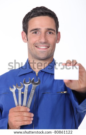 a 35 years old mechanic is showing a business card - stock photo