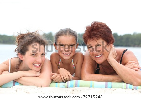 a 30 years old woman, a little girl and a 55 years old woman lying down on the beach, behind sea and forest background