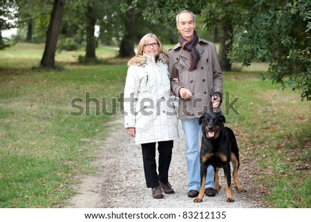 a 60 years old woman holding husband's arm in a park in autumn,  the man is keeping a dog on the leash - stock photo