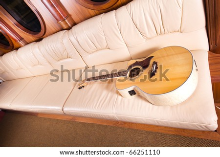 a yellow acoustic guitar on sofa - stock photo