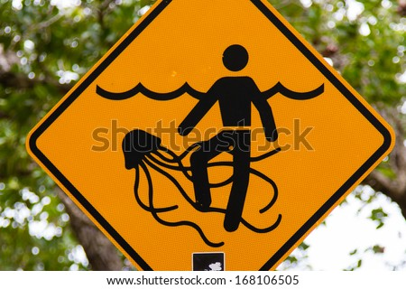 A yellow and black warning sign for dangerous marine stingers or jellyfish in tropical Australia. - stock photo