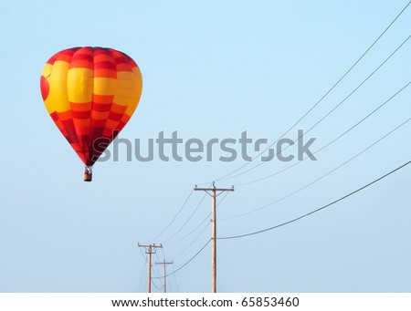 A yellow and red hot air balloon floats over a row of electrical power lines. - stock photo