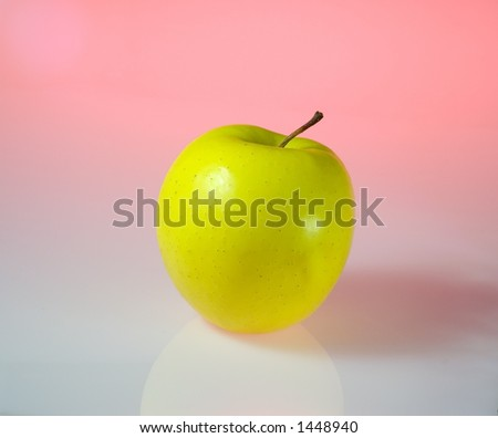 A yellow apple isolated in light pink background - stock photo