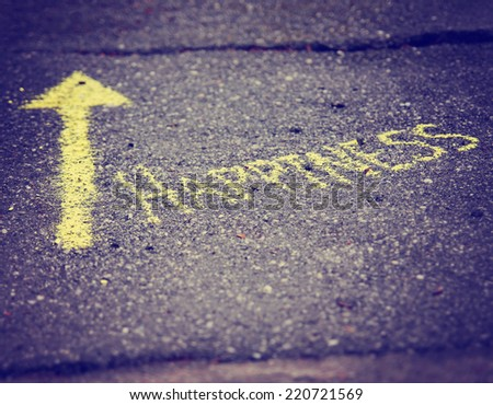 a yellow arrow showing the way to happiness written on a sidewalk with chalk toned with a retro vintage instagram filter effect (very shallow depth of field) - stock photo