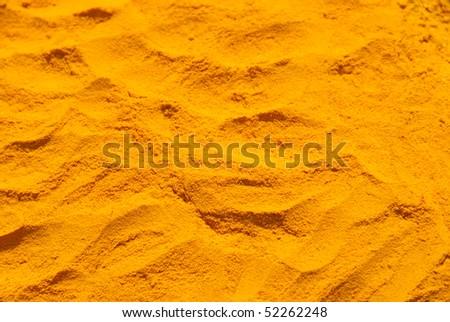 A yellow background - turmeric powder - stock photo