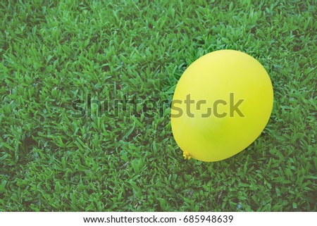 a yellow balloon on green lawn for background, filtered tones