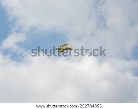 A yellow biplane in flight among the clouds - stock photo