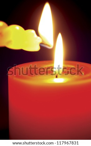 a yellow candle lighting up the red candle