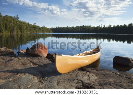 A yellow canoe rests on a rocky shore of a calm blue lake in the Boundary Waters of Minnesota - stock photo