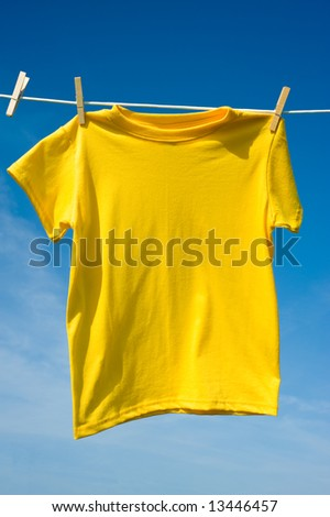 A yellow colored T-shirts hanging on a clothesline on a beautiful, sunny day, add text or graphic to shirts or copy space - stock photo