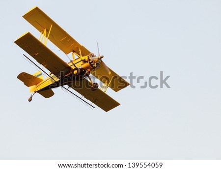 A yellow crop duster from below - stock photo