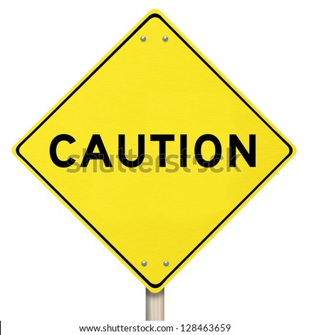 A yellow diamond-shaped road sign cautions people - stock photo