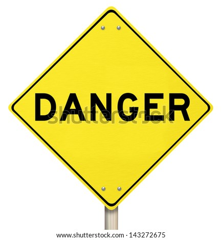 A yellow diamond-shaped road sign cautions people that Danger is ahead - stock photo