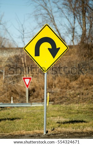 A yellow directional sign with black arrow directing to go right and back.
