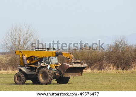 a yellow farm loader in a field in springtime