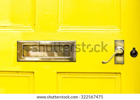 A yellow front door with a metal letterbox and handle - stock photo