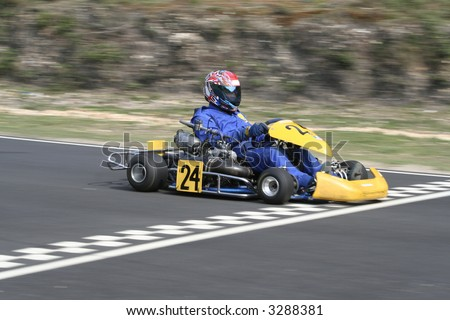 A yellow gearbox go kart crossing the finish line - stock photo
