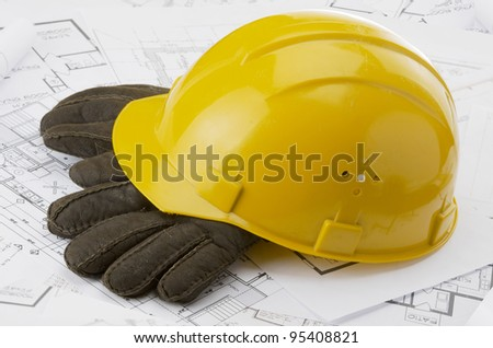 A yellow hard hat over a construction drawing - stock photo