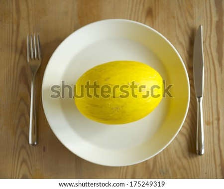 A yellow honeydew melon on a white plate with cutlery